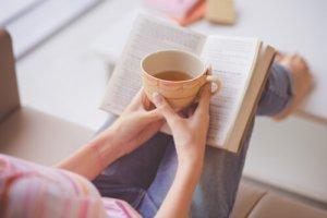 ספר וכוס קפה על רלגיים של אישה